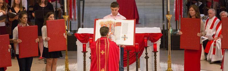 Fr. Hendrickson blesses volumes of the St. John's Bible at the Mass of the Holy Spirit, Sept. 2015.
