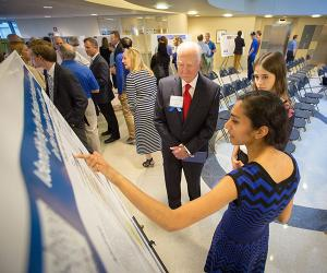 Undergraduate student presenting research poster to Dr. George Haddix